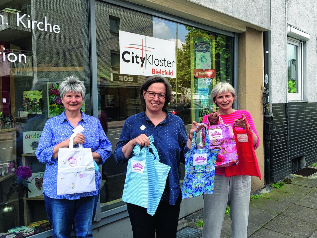 """Vor dem CityKloster-Laden in der Bielefelder Altstadt präsentieren Annette Steinkühler, Susanne Kochannek und Bärbel Lödige (v.l.) die """"Bumerang-Taschen"""". (Foto: Barbara Handt)"""